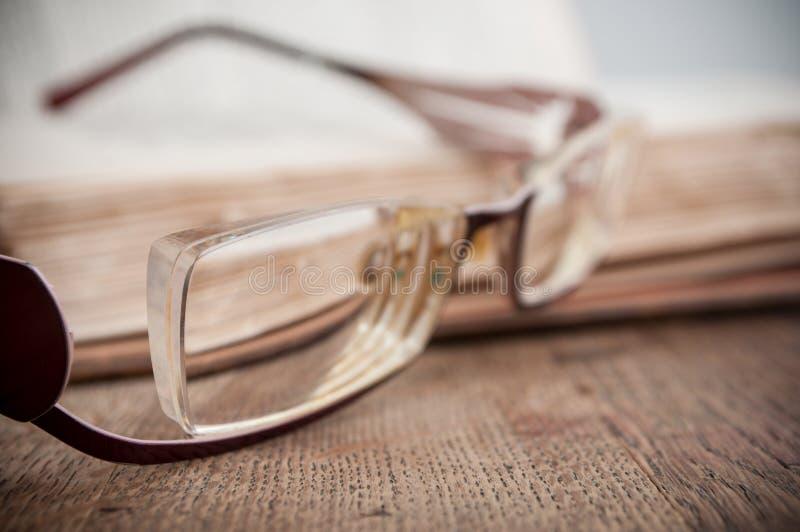 在古老书的玻璃在木桌backgrou打开 库存照片