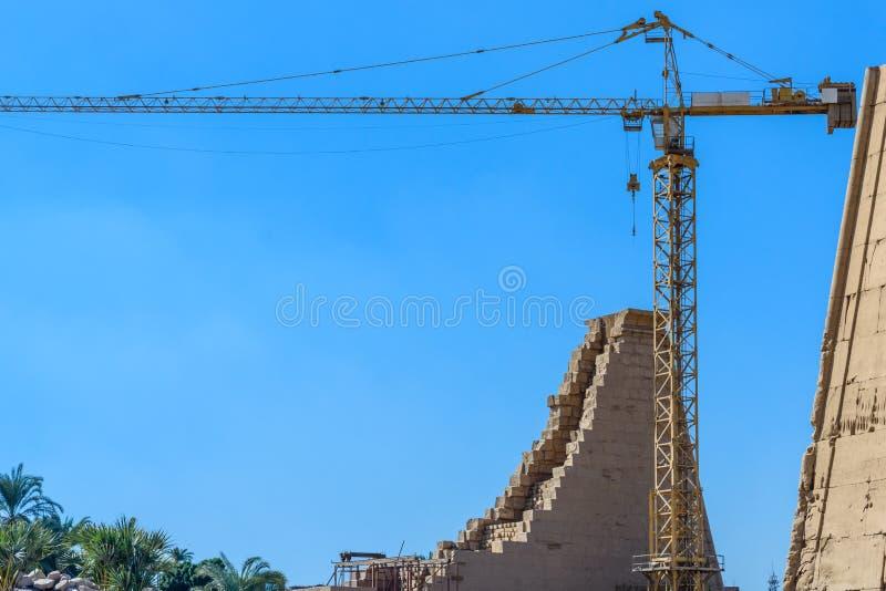 在古老卡尔纳克寺庙的废墟的高起重机 埃及卢克索 免版税图库摄影