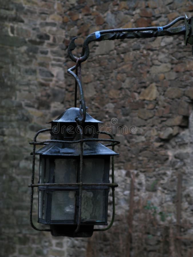 在古老城镇城堡一个石墙上的被风化的老铁加工的灯笼  免版税库存图片