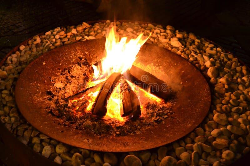 在古老外在圆的底部里面的火,由铁大盘制成 库存图片