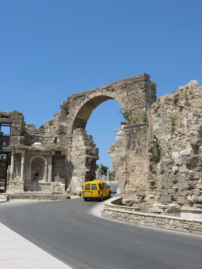 在古老曲拱下的黄色汽车通行证 免版税库存图片
