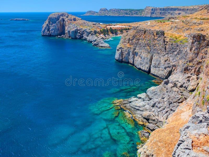 在古老珊瑚石岩石的美丽的景色在近大海海对风筝在希腊海岛上的沙子海滩 希腊海岛假日VA 库存照片