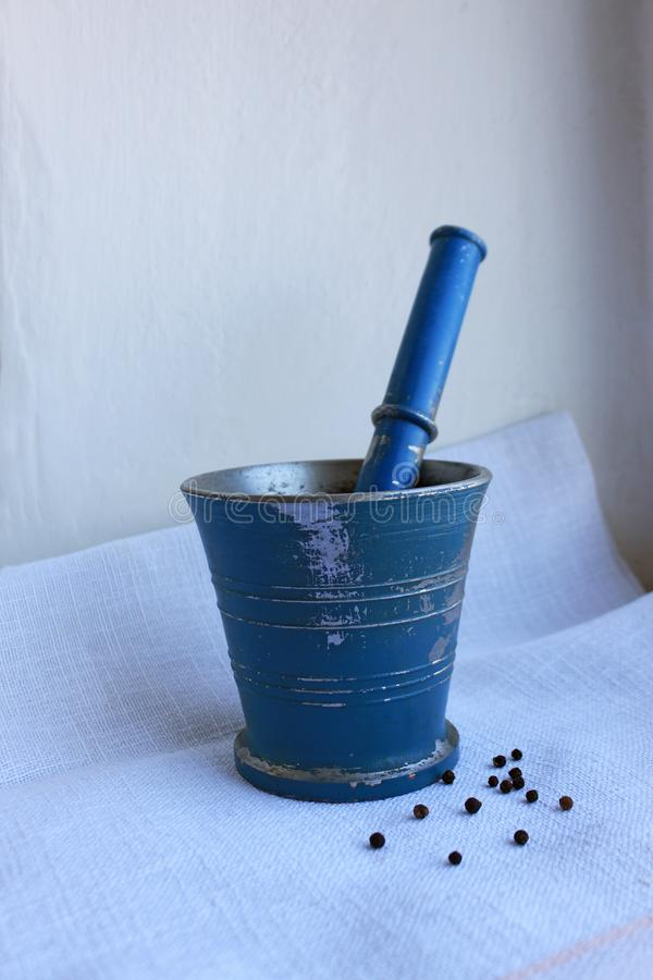 在古老金属灰浆的黑干胡椒与在亚麻制背景的杵 免版税库存照片