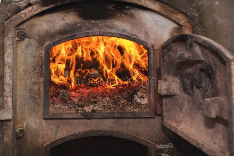 在古老铁锈火炉的火木头 库存图片