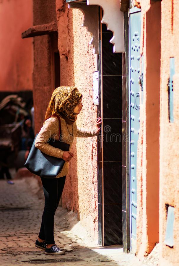在古老Fes麦地那的美好的回教女孩步行与传统平纹细布礼服,Fes,摩洛哥 免版税图库摄影