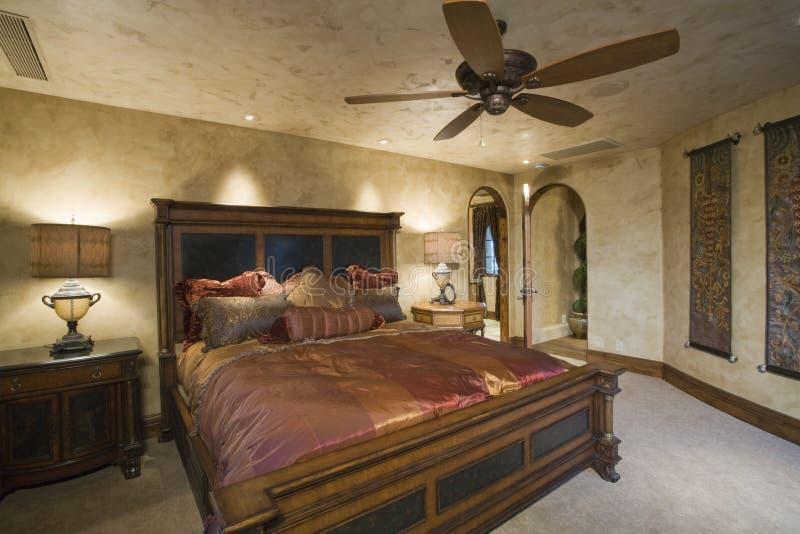 在古色古香的床上的丝绸床罩在家 库存照片