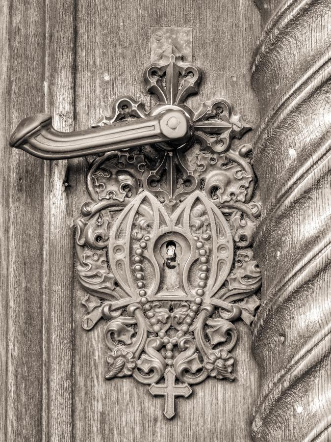 在古色古香的门的葡萄酒门把与十字架 库存照片