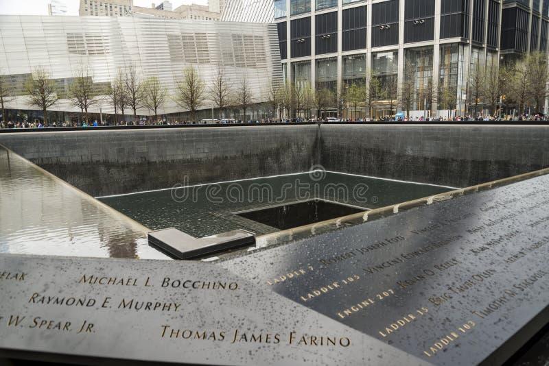 在古铜色墙壁上题写的受害者的名字围拢南塔脚印在9 11纪念品 图库摄影