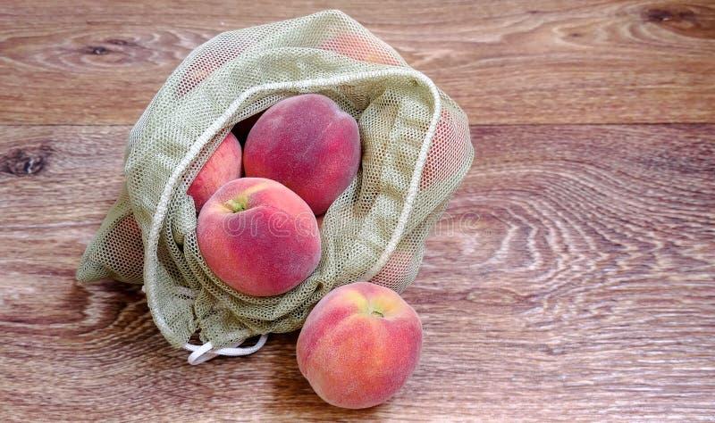 在可再用的eco袋子的成熟桃子 库存照片