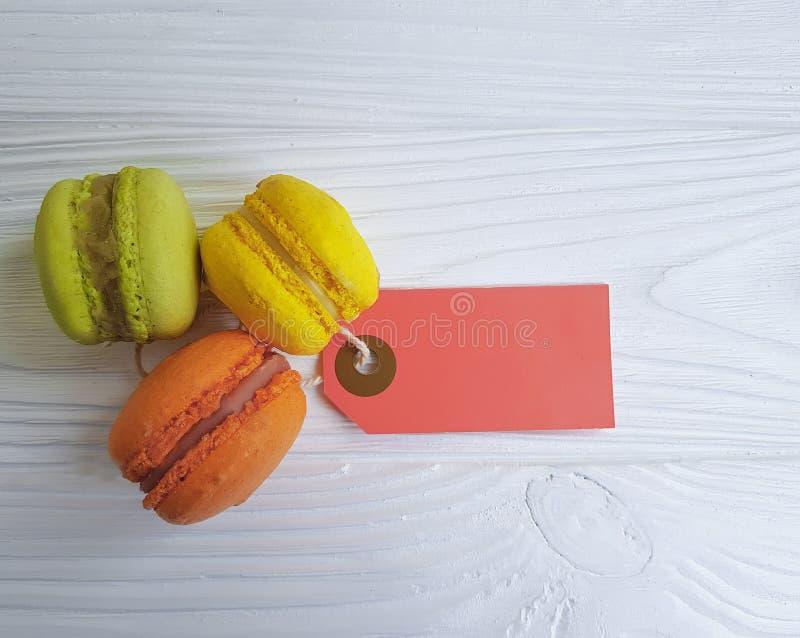 在可口白色木背景法国的标记的Macaron甜点 免版税库存照片