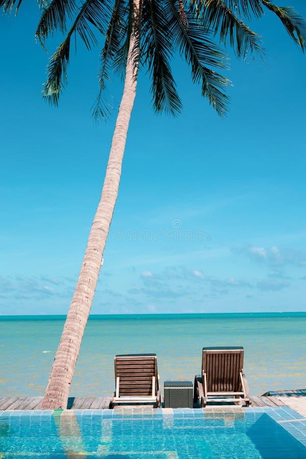 在可可椰子下的海滩睡椅在海假期概念附近 免版税库存照片