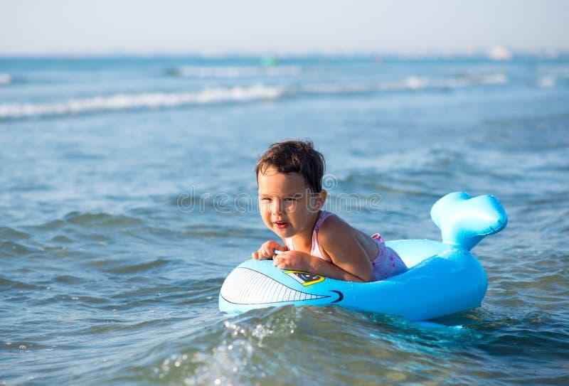在可膨胀的小女孩游泳在海 免版税图库摄影