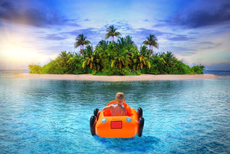 在可膨胀的汽车的小男孩游泳到热带海岛 库存图片