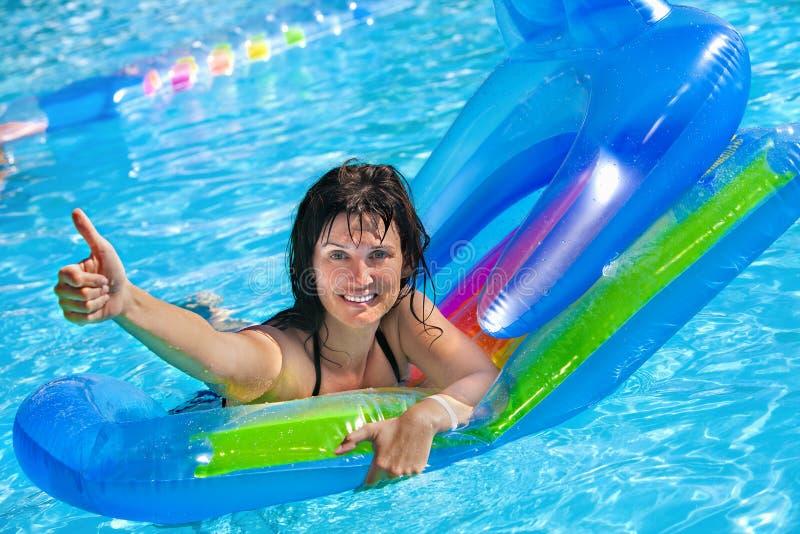 在可膨胀的海滩床垫的妇女游泳 免版税图库摄影