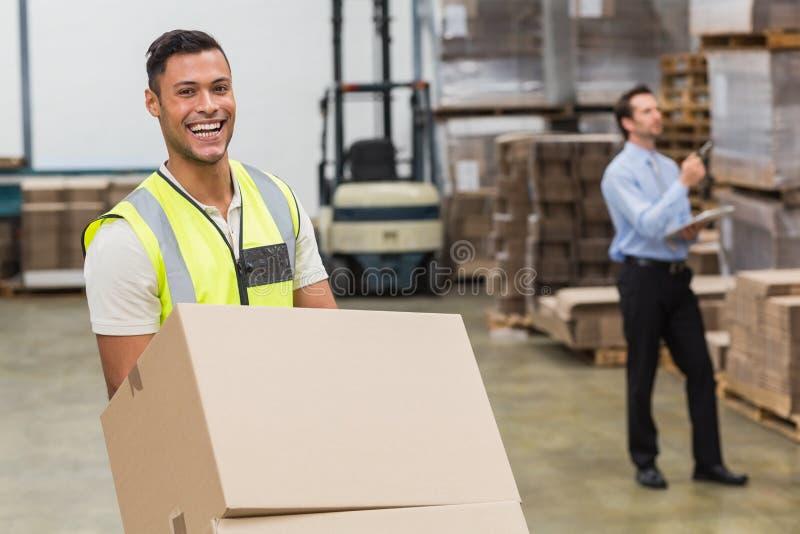 在台车的微笑的仓库工作者移动的箱子 库存照片