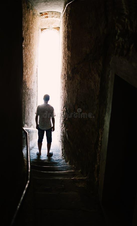 在台阶的人剪影在狭窄的街道 库存照片