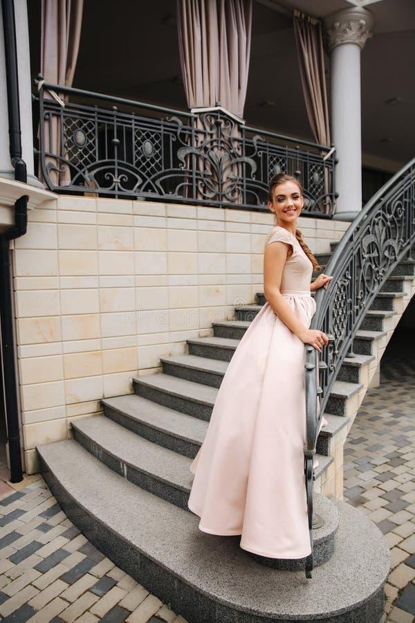 在台阶的典雅的夫人satnd在餐馆前面 库存照片