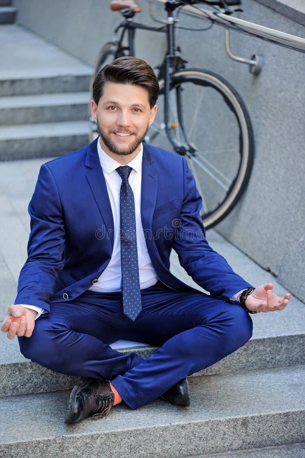 年轻在台阶的商人实践的瑜伽 免版税库存图片