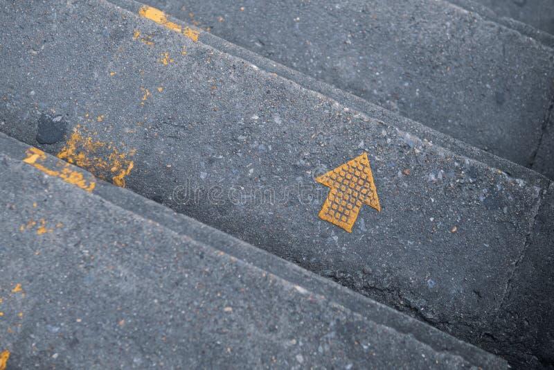 在台阶的黄色箭头,保留正确的标志 免版税库存图片