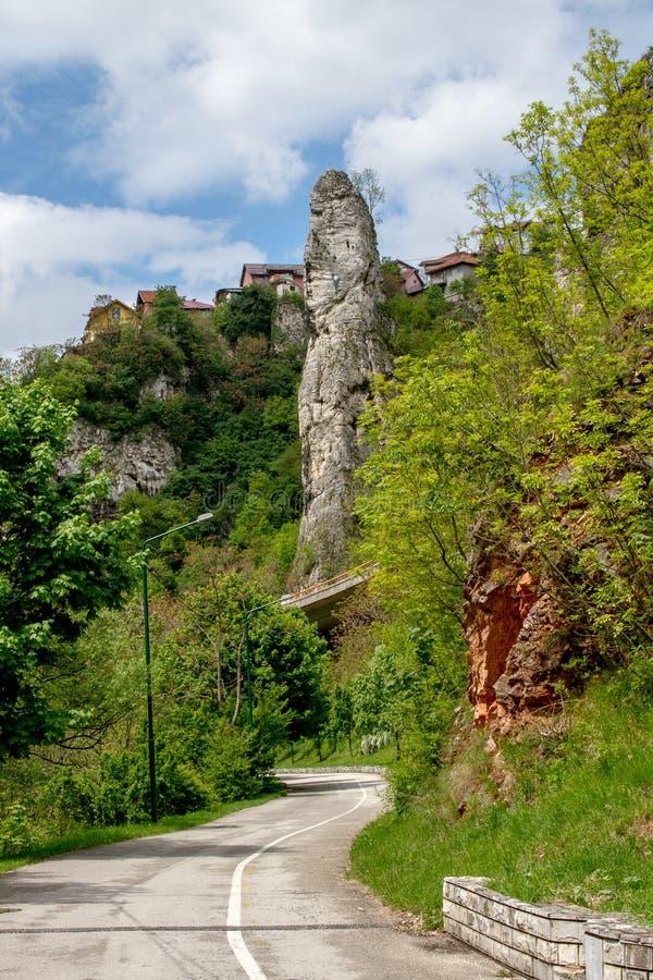 在史诗天空下的山路轮与类似石峭壁的云彩和阴茎 库存图片