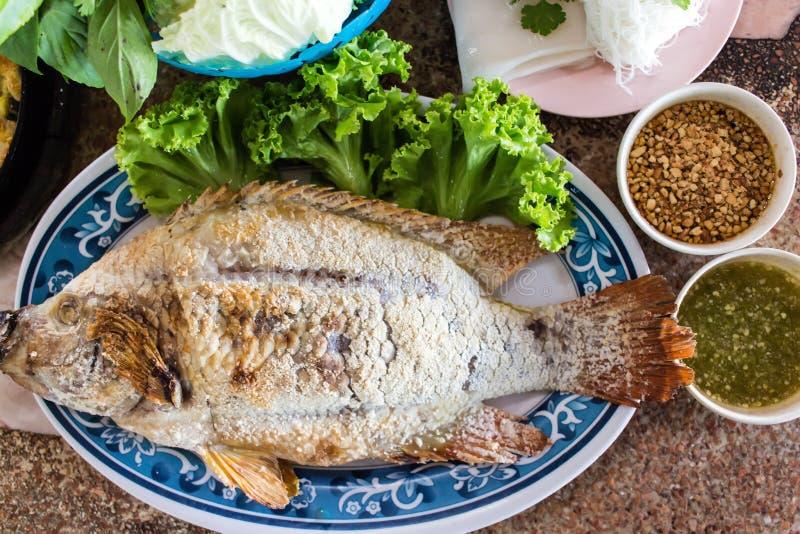 在叶子和烤红宝石鱼包裹的食物 库存照片
