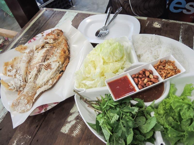 在叶子和烤鱼包裹的食物 免版税库存照片