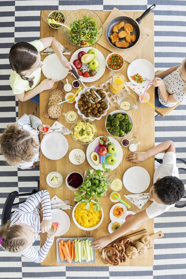 在吃健康晚餐的孩子的顶视图在生日期间 免版税库存照片