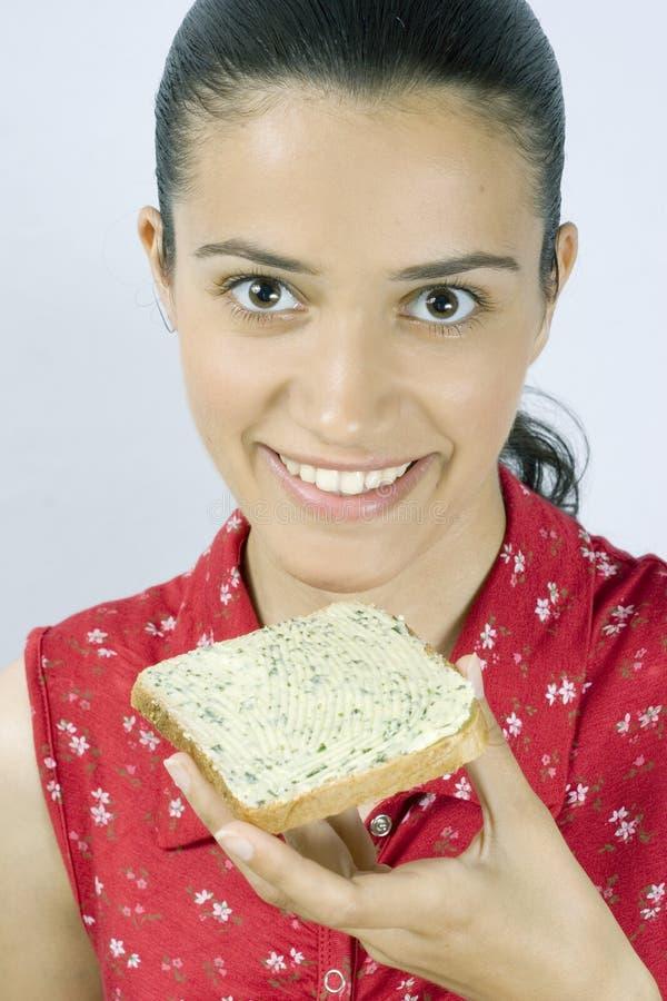 在吃女孩片式上添面包 免版税库存图片
