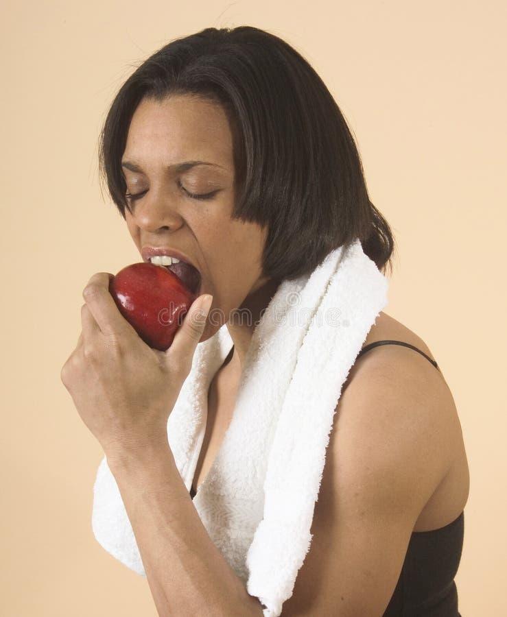 在吃适应附近的苹果她的肩膀毛巾妇女年轻人 库存图片