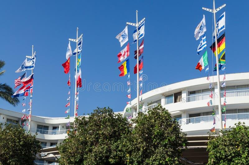 在各种各样的国家明亮,振翼的旗子反对蓝天和旅馆,埃拉特,以色列的底视图 库存照片