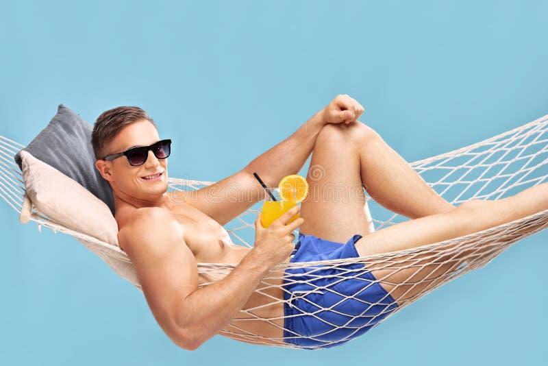 在吊床和拿着鸡尾酒的赤裸上身的人 免版税库存图片