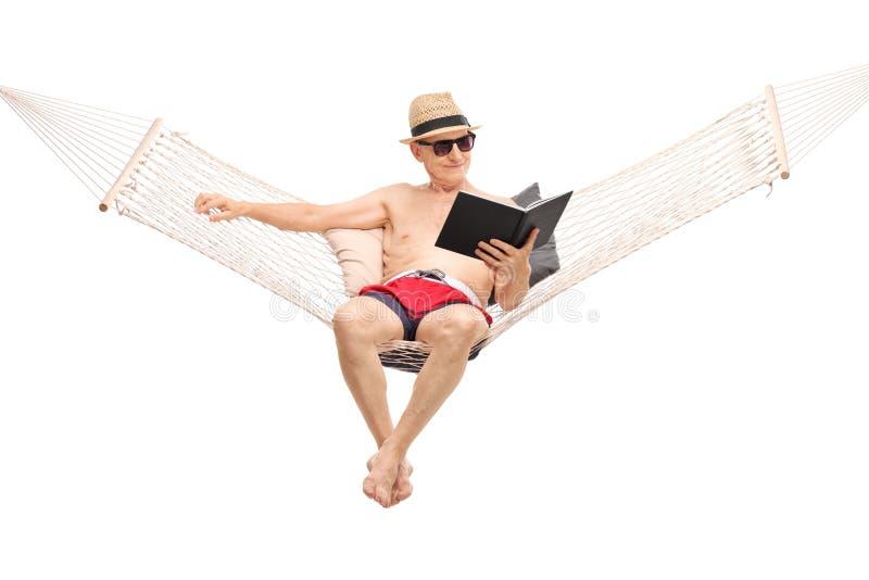 在吊床和阅读书的轻松的资深开会 库存照片