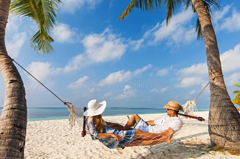 在吊床在马尔代夫,热带海滩的年轻白种人夫妇 图库摄影