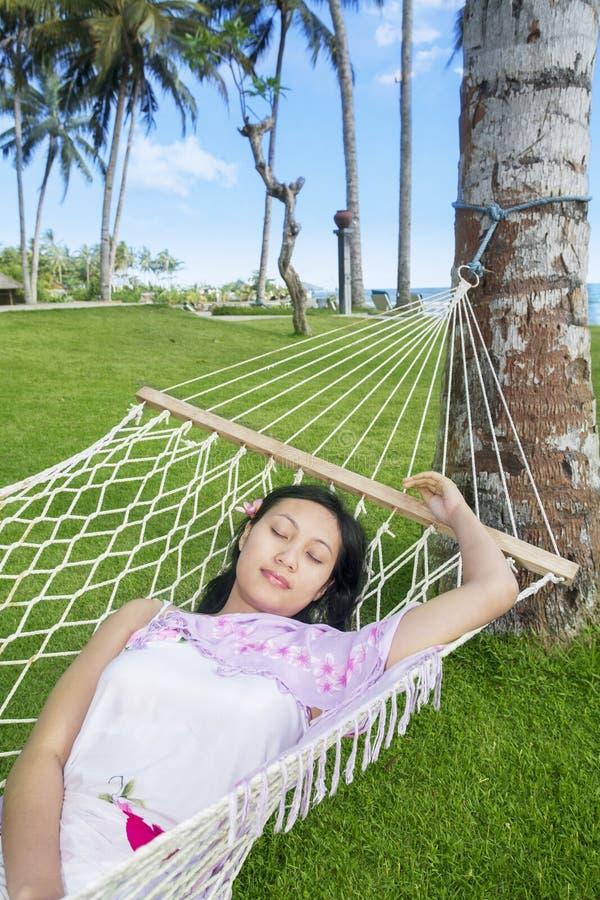 在吊床的亚洲妇女睡眠在海滩 库存照片