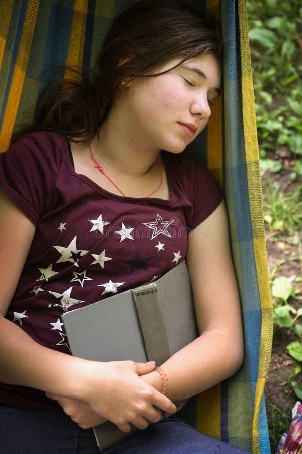 在吊床的内向少年女孩阅读书 库存照片
