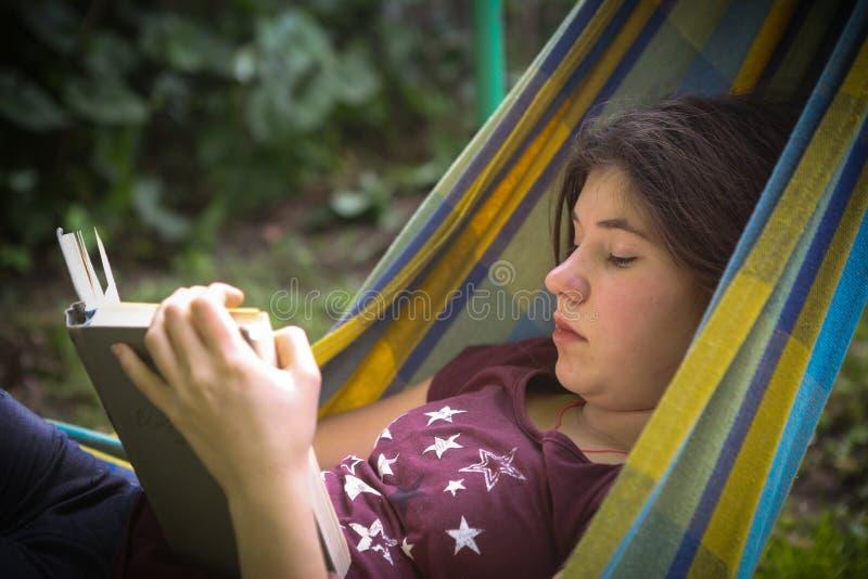 在吊床的内向少年女孩阅读书 免版税图库摄影