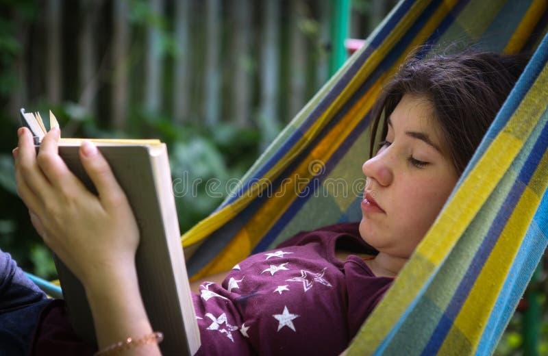 在吊床的内向少年女孩阅读书 图库摄影