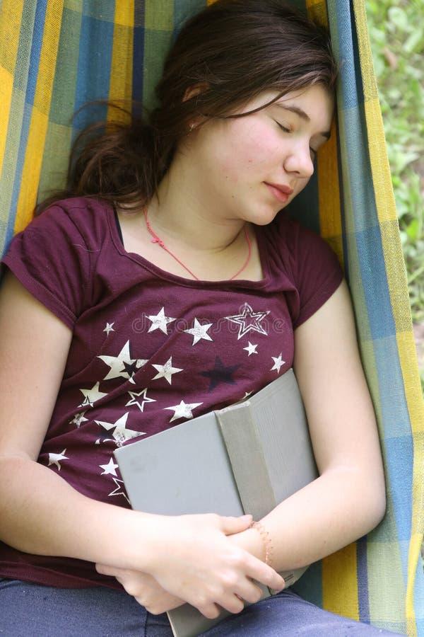 在吊床的内向少年女孩阅读书 免版税库存图片