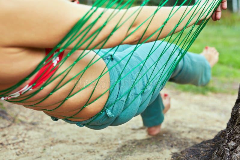 在吊床的女性身体 免版税图库摄影