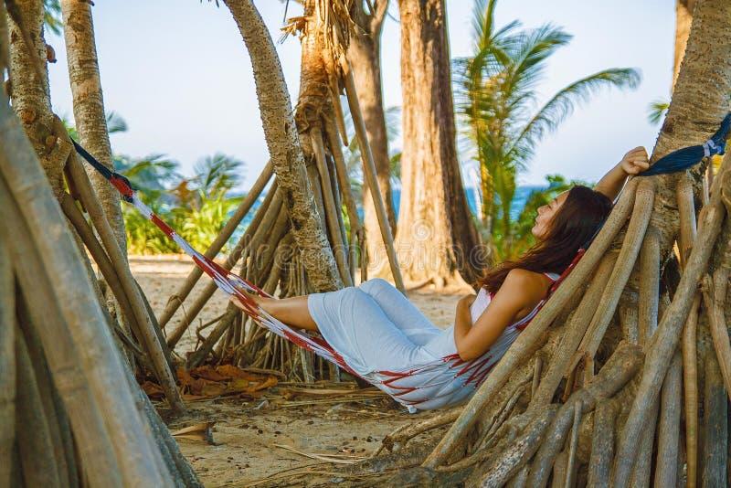 在吊床的画象美好的年轻亚洲妇女幸福微笑休闲在海滩海和海洋附近摇摆有天空蔚蓝白色云彩的 免版税库存图片