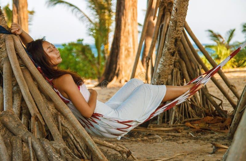 在吊床的画象美好的年轻亚洲妇女幸福微笑休闲在海滩海和海洋附近摇摆有天空蔚蓝白色云彩的 库存照片