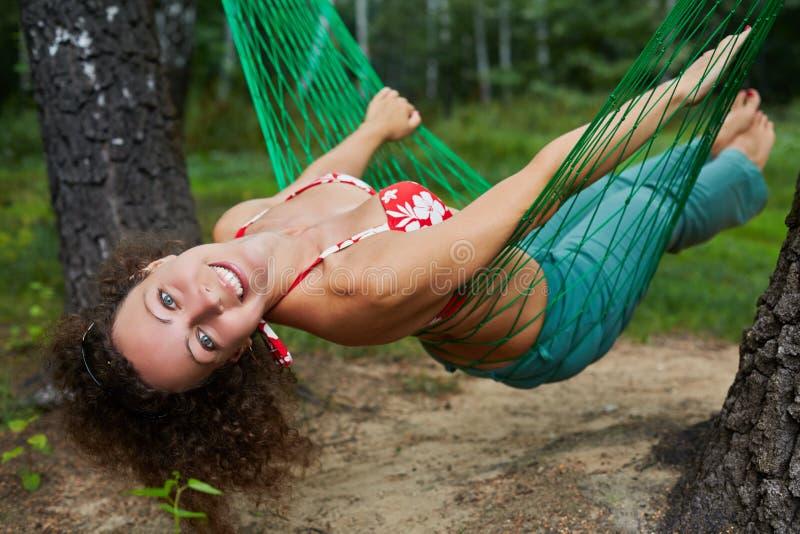 在吊床的年轻人微笑的赤足妇女摇摆 免版税库存照片