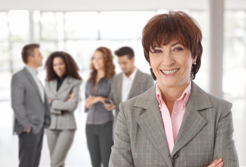 在同事前面的中年女实业家 免版税库存图片