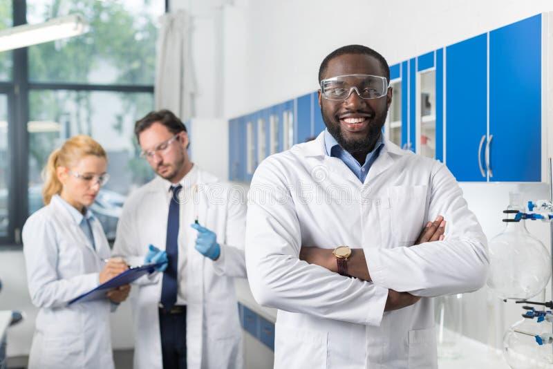 在同事前面的愉快的微笑的非裔美国人的科学家立场在记录下来的实验室实验或 库存图片