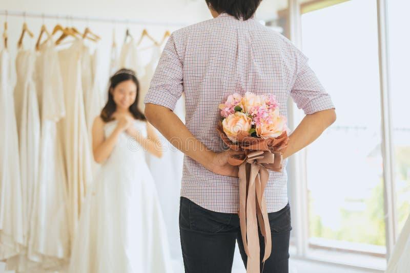 在后的新郎掩藏的花为了使新娘,妇女正面情感惊奇和面对吃惊的愉快和smling 免版税库存照片