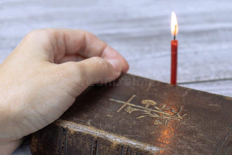 在后边圣经dook和灼烧的红色教会蜡烛的女性手 免版税库存照片