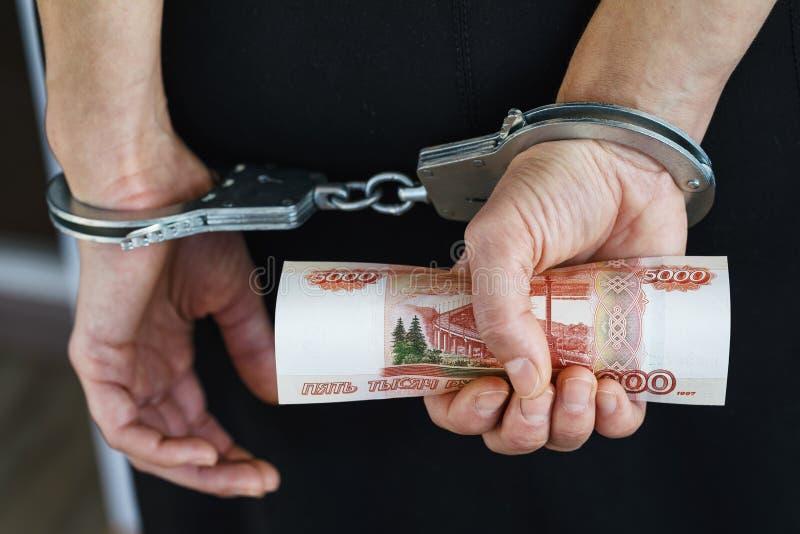 在后边手铐的手,拿着五千卢布 库存照片