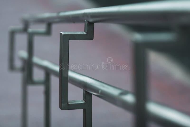 在后退入与选择聚焦的距离的街道上的不锈钢扶手栏杆 库存照片