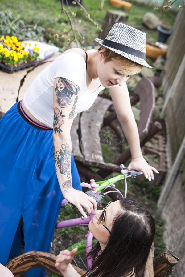 在后院谈和享受天的两个女孩朋友 免版税图库摄影