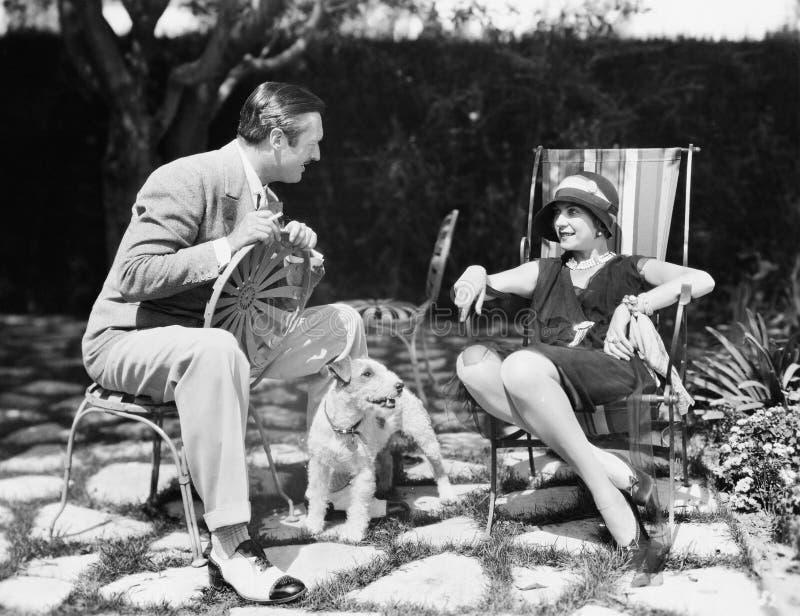 在后院结合坐谈话与在他们之间的一条狗(所有人被描述不更长生存,并且庄园不存在 库存照片